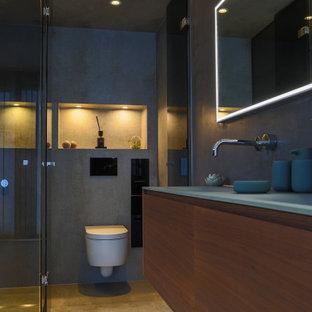 Cette image montre une grand salle de bain principale minimaliste avec un placard à porte plane, des portes de placard en bois sombre, une baignoire posée, une douche à l'italienne, un WC suspendu, un carrelage gris, un carrelage de pierre, un mur gris, un sol en carreaux de ciment, un lavabo intégré, un plan de toilette en verre, un sol beige, aucune cabine, un plan de toilette vert, un banc de douche, meuble double vasque, meuble-lavabo suspendu, un plafond décaissé et boiseries.