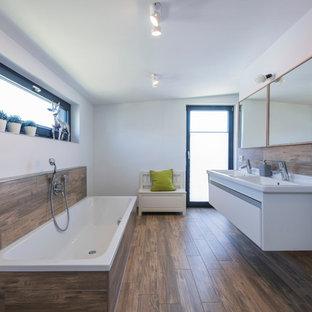 Mittelgroßes Modernes Badezimmer En Suite mit flächenbündigen Schrankfronten, weißen Schränken, Einbaubadewanne, Duschbadewanne, weißer Wandfarbe, braunem Holzboden und integriertem Waschbecken in Sonstige