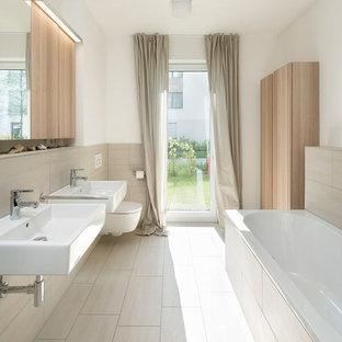 Mittelgroßes Modernes Badezimmer mit Einbaubadewanne, Wandtoilette, beigefarbenen Fliesen, weißer Wandfarbe und Wandwaschbecken in Berlin