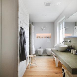 Diseño de cuarto de baño escandinavo, grande, con bidé, paredes grises, suelo de madera en tonos medios, lavabo sobreencimera y encimera de cemento