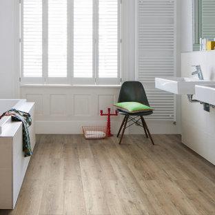 Modernes Badezimmer mit Einbaubadewanne, weißen Fliesen, weißer Wandfarbe, braunem Holzboden, Wandwaschbecken und braunem Boden in München