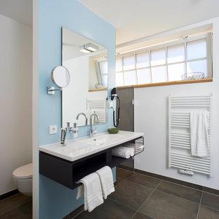 Mittelgroßes Modernes Duschbad mit offenen Schränken, schwarzen Schränken, blauer Wandfarbe und integriertem Waschbecken in Hannover