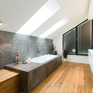 Mittelgroßes Modernes Duschbad mit flächenbündigen Schrankfronten, weißen Schränken, Einbaubadewanne, grauen Fliesen, Keramikfliesen, weißer Wandfarbe, braunem Holzboden, integriertem Waschbecken und braunem Boden in München