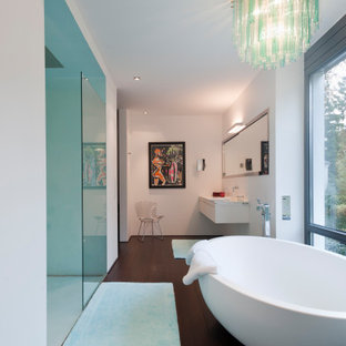 Großes Modernes Badezimmer En Suite mit flächenbündigen Schrankfronten, weißen Schränken, freistehender Badewanne, Duschnische, weißer Wandfarbe, Unterbauwaschbecken, braunem Boden, weißer Waschtischplatte, Einzelwaschbecken und schwebendem Waschtisch in München