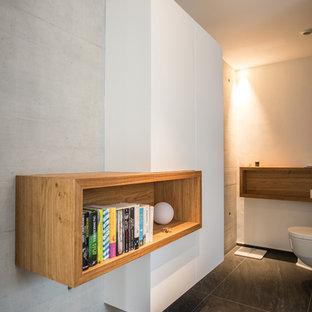Mittelgroßes Modernes Badezimmer mit flächenbündigen Schrankfronten, weißen Schränken, Wandtoilette, weißer Wandfarbe und schwarzem Boden in Stuttgart