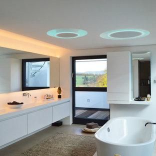 Foto de cuarto de baño actual, grande, con armarios con paneles lisos, puertas de armario blancas, bañera exenta, paredes blancas y lavabo integrado