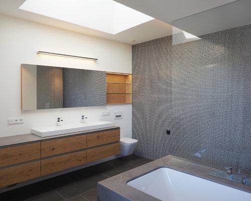 Mittelgroßes Modernes Badezimmer Mit Flächenbündigen Schrankfronten,  Hellbraunen Holzschränken, Bodengleicher Dusche, Wandtoilette, Schwarzen