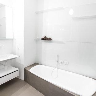 Пример оригинального дизайна: маленькая ванная комната в стиле модернизм с подвесной раковиной, плоскими фасадами, белыми фасадами, накладной ванной, инсталляцией, белыми стенами, белой плиткой, плиткой из листового стекла и бетонным полом