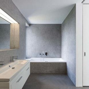 Mittelgroßes Modernes Badezimmer En Suite mit flächenbündigen Schrankfronten, weißen Schränken, Einbaubadewanne, grauen Fliesen, grauer Wandfarbe, Betonboden, Aufsatzwaschbecken und Mineralwerkstoff-Waschtisch in Sonstige
