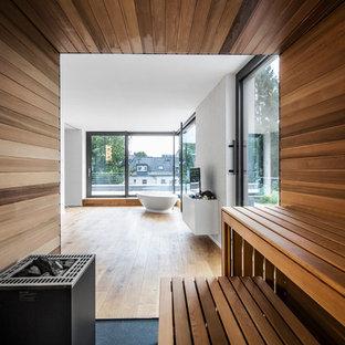 Geräumiges Modernes Badezimmer Mit Freistehender Badewanne, Weißer  Wandfarbe, Braunem Holzboden Und Sauna In Köln