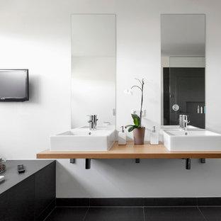 ケルンの広いコンテンポラリースタイルのおしゃれな浴室 (ベッセル式洗面器、ドロップイン型浴槽、白い壁、スレートの床、木製洗面台) の写真