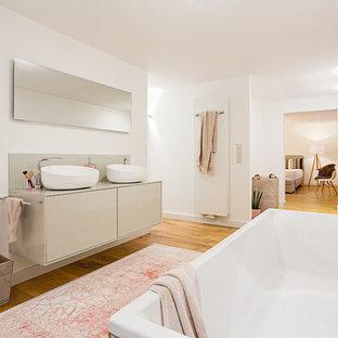 Réalisation d'une très grand salle de bain principale design avec un placard à porte plane, des portes de placard beiges, une baignoire posée, une douche à l'italienne, un WC suspendu, un carrelage beige, carrelage en mosaïque, un mur blanc, un sol en bois brun, une vasque, un plan de toilette en surface solide, un sol marron et un plan de toilette beige.