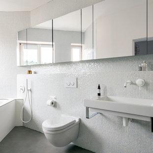Idee per una piccola stanza da bagno contemporanea con vasca sottopiano, WC sospeso, piastrelle a mosaico, pareti bianche, lavabo sospeso e pavimento in cemento