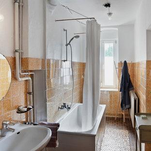 Modelo de cuarto de baño tradicional, de tamaño medio, con bañera encastrada sin remate, combinación de ducha y bañera, baldosas y/o azulejos naranja, baldosas y/o azulejos de cerámica, parades naranjas, suelo de baldosas de cerámica y lavabo suspendido