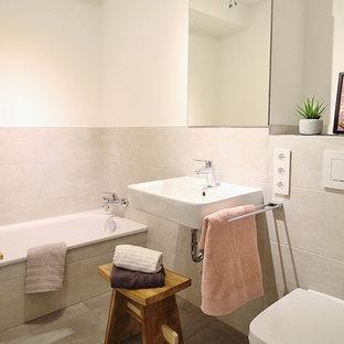 Kleines Nordisches Duschbad mit offenen Schränken, Badewanne in Nische, Wandtoilette, grauen Fliesen, beiger Wandfarbe, Wandwaschbecken, grauem Boden, Zementfliesen und Zementfliesen in Hamburg