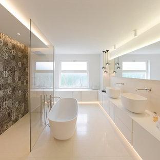 Großes Modernes Badezimmer En Suite mit freistehender Badewanne, bodengleicher Dusche, Keramikboden, Mineralwerkstoff-Waschtisch, offener Dusche, flächenbündigen Schrankfronten, weißen Schränken, farbigen Fliesen, weißer Wandfarbe, Aufsatzwaschbecken, weißem Boden und weißer Waschtischplatte in Stuttgart