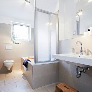 Kleines Modernes Duschbad mit Einbaubadewanne, Duschbadewanne, Wandtoilette, beigefarbenen Fliesen, Zementfliesen, weißer Wandfarbe, Zementfliesen, Wandwaschbecken, beigem Boden und Falttür-Duschabtrennung in Nürnberg