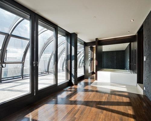 Modernes Badezimmer En Suite Mit Badewanne In Nische, Schwarzer Wandfarbe  Und Dunklem Holzboden In Berlin