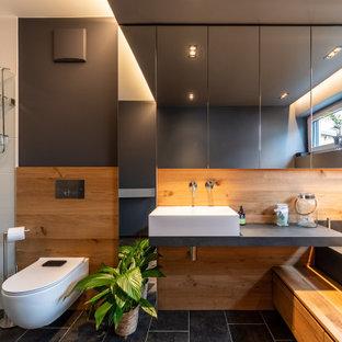 Mittelgroßes Modernes Duschbad mit Wandtoilette, braunen Fliesen, Porzellanfliesen, schwarzer Wandfarbe, Porzellan-Bodenfliesen, Aufsatzwaschbecken, schwarzem Boden, grauer Waschtischplatte, Einzelwaschbecken und schwebendem Waschtisch in München