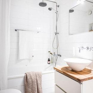 Modern inredning av ett litet beige beige badrum med dusch, med släta luckor, vita skåp, ett fristående badkar, en dusch i en alkov, vit kakel, porslinskakel, klinkergolv i porslin, ett fristående handfat, träbänkskiva, grått golv och dusch med duschdraperi
