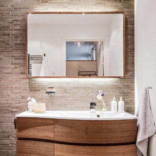 Modern inredning av ett badrum, med släta luckor, skåp i mellenmörkt trä, brun kakel, stickkakel, vita väggar, ett integrerad handfat och brunt golv