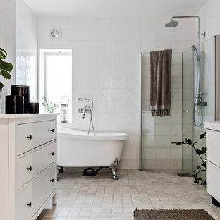 Minimalistisk inredning av ett en-suite badrum, med släta luckor, vita skåp, ett badkar med tassar, en hörndusch, vit kakel, vita väggar, beiget golv och dusch med gångjärnsdörr