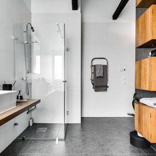 Idéer för ett stort modernt badrum med dusch, med skåp i mellenmörkt trä, en kantlös dusch, en toalettstol med hel cisternkåpa, vit kakel, porslinskakel, vita väggar, ett fristående handfat, träbänkskiva, släta luckor och dusch med gångjärnsdörr