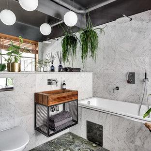 Foto på ett mellanstort funkis en-suite badrum, med öppna hyllor, ett platsbyggt badkar, en dusch/badkar-kombination, en vägghängd toalettstol, vit kakel, skåp i mellenmörkt trä, grå väggar, marmorgolv och ett fristående handfat