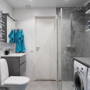 Idee per una stanza da bagno nordica di medie dimensioni con ante lisce, ante grigie, doccia ad angolo, WC monopezzo, porta doccia a battente, piastrelle grigie, piastrelle bianche, pareti grigie, pavimento grigio e lavanderia