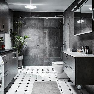 Inredning av ett modernt mellanstort badrum med dusch, med släta luckor, skåp i mellenmörkt trä, en toalettstol med hel cisternkåpa, grå kakel, keramikplattor, klinkergolv i keramik, ett avlångt handfat, laminatbänkskiva, dusch med gångjärnsdörr, en dusch i en alkov, grå väggar och vitt golv