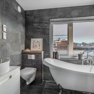 Inredning av ett modernt mellanstort vit vitt badrum, med släta luckor, vita skåp, ett badkar med tassar, en dusch/badkar-kombination, en vägghängd toalettstol, grå kakel, skifferkakel, grå väggar, skiffergolv, ett fristående handfat, bänkskiva i kvarts, grått golv och med dusch som är öppen