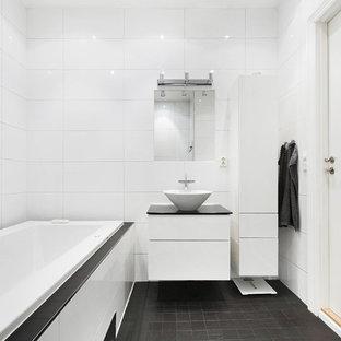 Idéer för att renovera ett mellanstort nordiskt svart svart badrum, med släta luckor, vita skåp, ett platsbyggt badkar, vit kakel, vita väggar, ett fristående handfat och svart golv