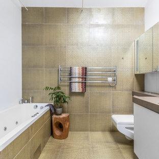 Ejemplo de cuarto de baño contemporáneo, de tamaño medio, con armarios con paneles lisos, puertas de armario blancas, combinación de ducha y bañera, sanitario de pared, baldosas y/o azulejos beige, baldosas y/o azulejos amarillos, encimeras marrones, bañera encastrada, paredes blancas y suelo amarillo
