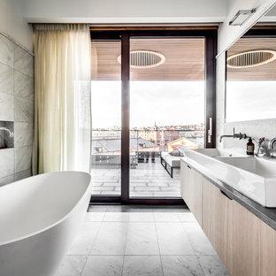 Inredning av ett modernt badrum, med släta luckor, skåp i ljust trä, ett fristående badkar, grå väggar, ett fristående handfat och grått golv