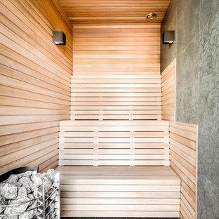 Foto på ett funkis bastu, med grå kakel, bruna väggar och grått golv