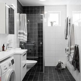 Exempel på ett skandinaviskt badrum med dusch, med släta luckor, vita skåp, en hörndusch, en vägghängd toalettstol, svart och vit kakel, ett konsol handfat, svart golv och dusch med gångjärnsdörr