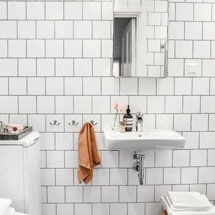 Пример оригинального дизайна: маленькая главная ванная комната в скандинавском стиле с плоскими фасадами, белой плиткой, керамогранитной плиткой, белыми стенами, полом из известняка и подвесной раковиной