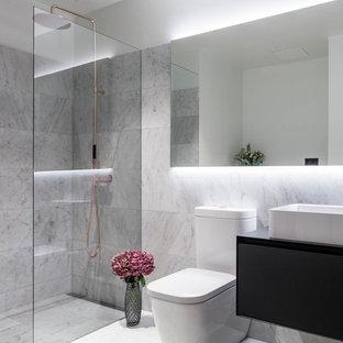 Ejemplo de cuarto de baño con ducha, escandinavo, grande, con ducha esquinera, sanitario de una pieza, baldosas y/o azulejos grises y ducha abierta