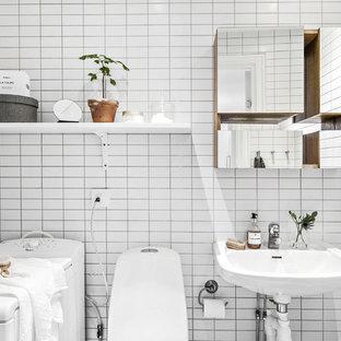 Foto på ett skandinaviskt badrum, med en toalettstol med hel cisternkåpa, vit kakel, vita väggar och ett väggmonterat handfat
