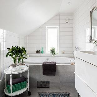 Immagine di una stanza da bagno con doccia nordica di medie dimensioni con ante bianche, vasca da incasso, pareti bianche, lavabo integrato, ante lisce, vasca/doccia, piastrelle diamantate e pavimento con piastrelle in ceramica