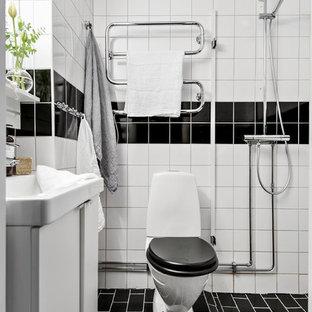 Inspiration för ett skandinaviskt badrum med dusch, med släta luckor, vita skåp, en öppen dusch, en toalettstol med separat cisternkåpa, svart och vit kakel, vita väggar, svart golv och med dusch som är öppen