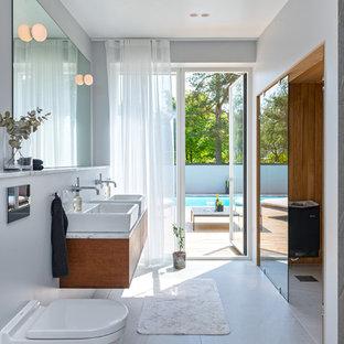 Foto på ett stort funkis en-suite badrum, med släta luckor, skåp i mörkt trä, grå väggar, ett fristående handfat och grått golv