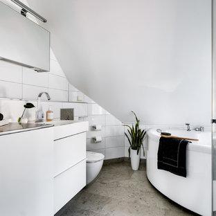 Idéer för minimalistiska grått en-suite badrum, med släta luckor, vita skåp, en jacuzzi, vit kakel, vita väggar, ett integrerad handfat, bänkskiva i rostfritt stål och grått golv