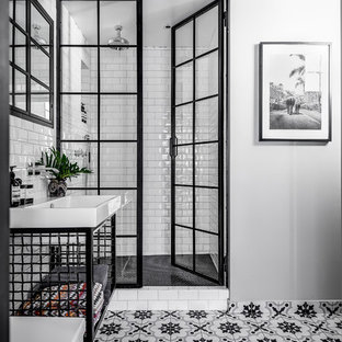 Example of a mid-sized urban white tile and subway tile ceramic floor and multicolored floor bathroom design in Stockholm with open cabinets, black cabinets, white walls, a drop-in sink and a hinged shower door