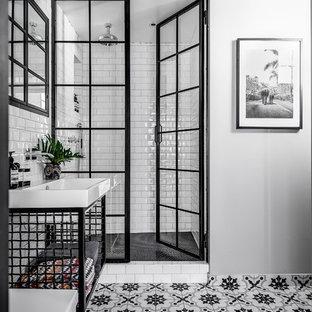 Foto på ett mellanstort industriellt badrum, med öppna hyllor, svarta skåp, vit kakel, tunnelbanekakel, vita väggar, klinkergolv i keramik, ett nedsänkt handfat, flerfärgat golv och dusch med gångjärnsdörr