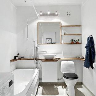 Esempio di una stanza da bagno scandinava di medie dimensioni con vasca/doccia, pareti bianche, pavimento in linoleum, lavabo a bacinella, top in legno, pavimento grigio, top marrone, ante lisce, ante bianche, vasca ad angolo, WC a due pezzi e doccia con tenda