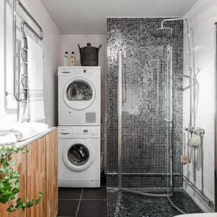 Nordisk inredning av ett badrum med dusch, med en hörndusch, en toalettstol med hel cisternkåpa, grå kakel, vit kakel, svart golv och dusch med gångjärnsdörr
