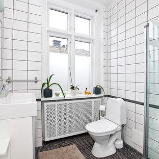 Modern inredning av ett mellanstort badrum med dusch, med en hörndusch, en toalettstol med separat cisternkåpa, svart kakel, vit kakel, vita väggar, ett integrerad handfat och porslinskakel