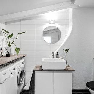 Idéer för att renovera ett minimalistiskt badrum med dusch, med släta luckor, vita skåp, en toalettstol med separat cisternkåpa, vit kakel, vita väggar, ett fristående handfat, träbänkskiva och svart golv