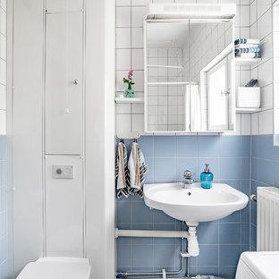 Inspiration för skandinaviska badrum med dusch, med släta luckor, vita skåp, en vägghängd toalettstol, blå kakel, vit kakel, blå väggar, ett väggmonterat handfat och dusch med duschdraperi